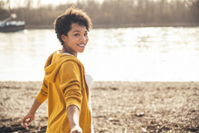 Young Woman Smiling While Standing By Lake On Sunny Day