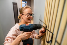Smiling Woman Using Drill Machine While Fixing Hook On Wall At Home