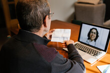 Senior Male Holding Prescription While Consultation On Video Call To Female Doctor At Home During COVID-19
