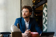 Thoughtful Businessman With Eyeglasses Looking Away While Having Food At Cafe