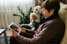 Grandparents On Video Call With Family Through Tablet At Home