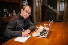 Senior Man Writing In Book While Using Laptop At Home