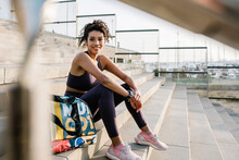 Smiling Sportsperson Day Dreaming While Sitting By Bag On Staircase