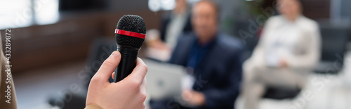Canvas Print lecturer holding microphone near blurred audience during seminar, banner