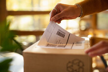 Close Up Business Owner Placing Shipping Label On Package