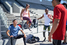 Young Athlete Friends Talking In Sunny Sports Stadium
