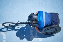 Male Wheelchair Athlete On Sunny Blue Sports Track
