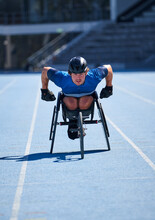 Focused Male Wheelchair Athlete Training On Sunny Blue Sports Track