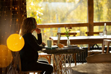Thoughtful Businesswoman Working At Table In Cafe