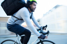 Male Bike Messenger Delivering Food Speeding On Road
