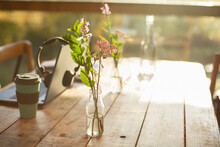 Simple Wildflower Arrangement In Glass Bottle On Rustic Cafe Table