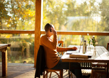 Businessman With Headphones Working At Laptop In Sunny Autumn Cafe