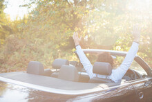 Carefree Young Man In Convertible In Sunny Autumn Park