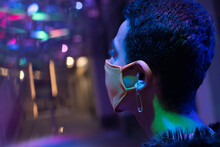 Young Man With Safety Pin Earring Wearing Face Mask In Nightclub