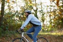 Happy Young Man Riding Bicycle In Autumn Park