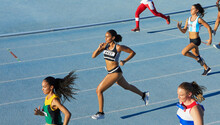 Female Track And Field Athletes Running In Competition On Blue Track