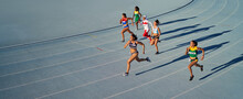 Female Track And Field Athletes Running In Race On Blue Track