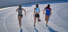 Female Track And Field Athletes Running In Competition On Track