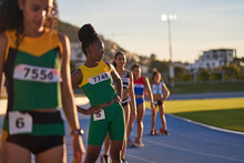 Female Track And Field Athletes Preparing At Starting Blocks On Track