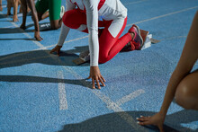 Female Track And Field Athletes At Starting Line On Blue Track