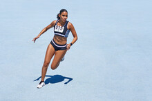Female Track And Field Athlete On Sunny Blue Track