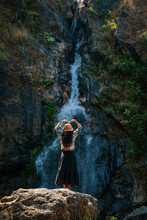 Woman Standing On A Rock With A Waterfall