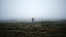 Full Length Rear View Of Man Hiking On A Steep Mountain In Fog