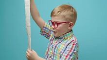 Preschool Kid Looking At Large Store Receipt And Getting Shocked, Then Turning To Camera And Smiling. Pretty Boy Wondering About High Expenses. Funny Home Budget Concept.
