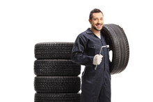 Smiling Auto Mechanic Man Holding A Tire And A Lug Wrench