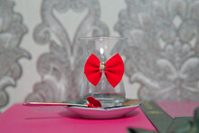 Tea In Azerbaijani Traditional Armudu Pear-shaped Glass . Filtered Tea For Engagement . Closed With A Red Ribbon . Check Bow Tie . Black Turkish Tea In Pear Shape Glass, Aromatic Tea In Armudu Cup .