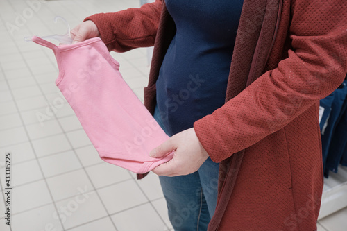Pregnant woman chooses a pink clothes - bodice for a baby in a store Fototapet