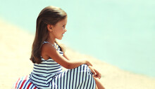 Summer Portrait Little Girl Child Sitting On A Sand Beach Looking At Sea