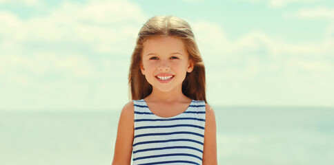 Summer portrait happy smiling little girl child wearing a striped dress on a beach on a sea background