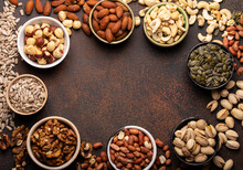 Selection Of Assorted Raw Nuts And Various Seeds In Bowls On Brown Stone Background From Above, Healthy Source Of Energy, Fat And Vegetarian Protein, Space For Text
