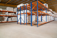Rows Of Shelves With Boxes, Huge Distribution Warehouse With High Shelves And Loaders