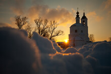 Orthodox Russian Church With Bell Tower In Snow Against The Background Of The Setting Evening Sun