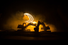 Construction Site On A City Street. A Yellow Digger Excavator Parked During The Night On A Construction Site. Industrial Concept Table Decoration On Dark Foggy Toned Background.
