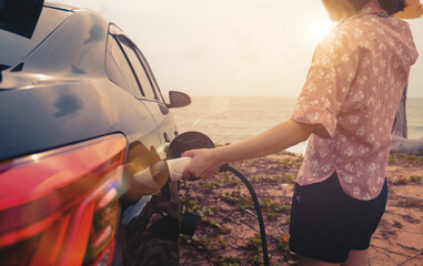 EV car charging power hybrid electric car at the charging station, hand holding charger inserting the pump, environmentally friendly lifestyle transportation vehicle traveling vacation evening sunset