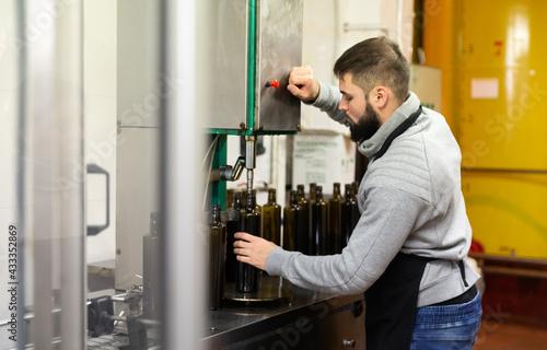 Obraz na plátně Young entrepreneur engaged in olive oil production, controlling process of bottl