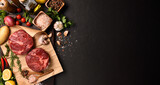 Fresh raw pieces of beef meat with ingredients for cooking on panorama black stone background