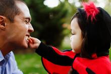 Girl Dressed As Ladybird Feeding Father