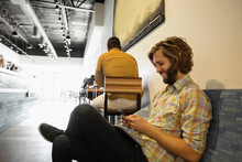 Young Man Sitting In Coffee Shop Using Smartphone