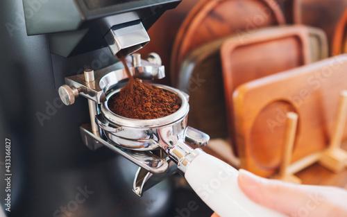 Fotografia Closeup image of barista grinding coffee in coffee shop