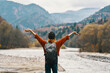 happy woman hiker with a backpack on the river bank look into the mountains and autumn forest nature