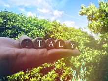 """Text """"Italy"""" Written On Wine Corks With The Italian Countryside Scenery As Background. Concept Of Travel To Italy."""