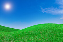 The Landscape Of Hills Is A Complex Green Grassland And A Blue Sky With The Sun Shining Down.