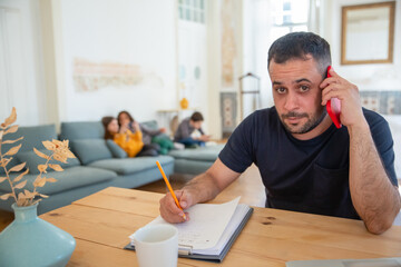 Focused Caucasian dad talking on phone and looking at camera. Bearded man working at home, sitting at table and writing information on paper. Fatherhood, work at home concept