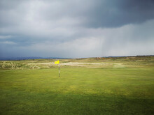Golf Course In The Rain With A Yellow Flag On The Green - Porthcawl.
