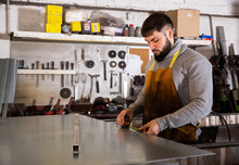 Skilled Man Worker Working With Measuring Tape In Workshop