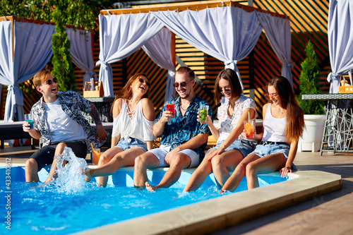 Stampa su Tela Group of friends having fun at poolside party clinking glasses with fresh cocktails splashing water by swimming pool on sunny summer day